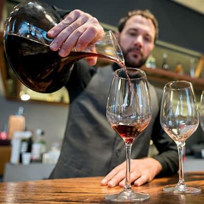 Man pouring wine at tasting room