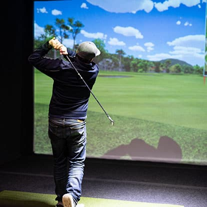 Man playing virtual golf at Back9 Parlor